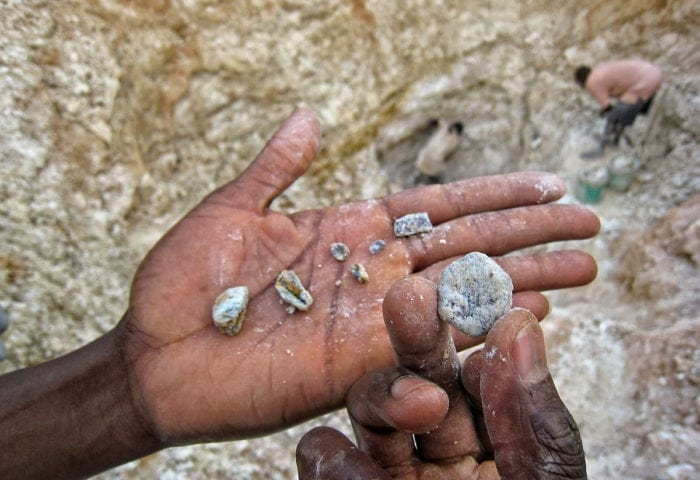 Fair trade rough diamonds being held by a person in East Africa, with one big diamond being shown up close.